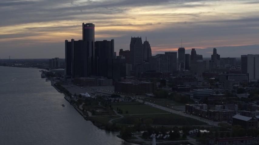 5.7K stock footage aerial video of GM Renaissance Center by the river and the city's skyline at sunset, Downtown Detroit, Michigan Aerial Stock Footage | DX0002_197_035