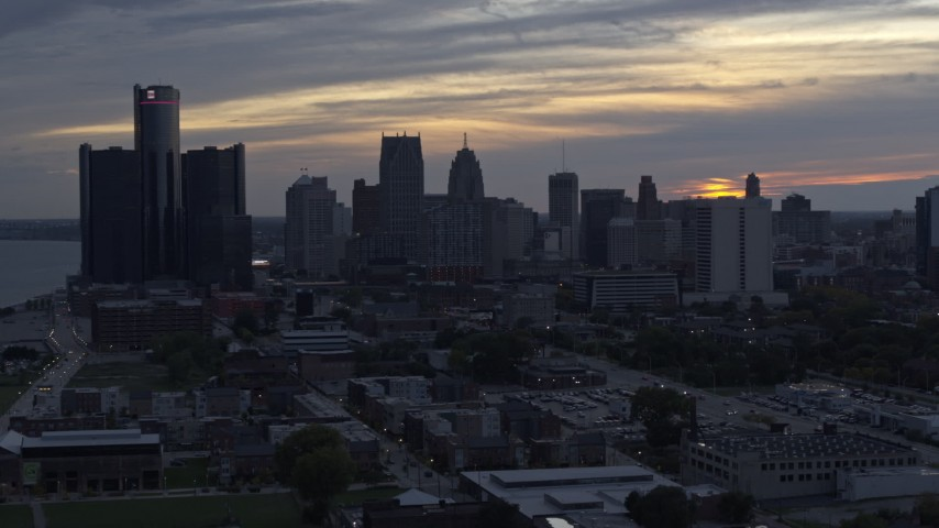 5.7K stock footage aerial video ascend away from GM Renaissance Center and the skyline at sunset, Downtown Detroit, Michigan Aerial Stock Footage | DX0002_197_038