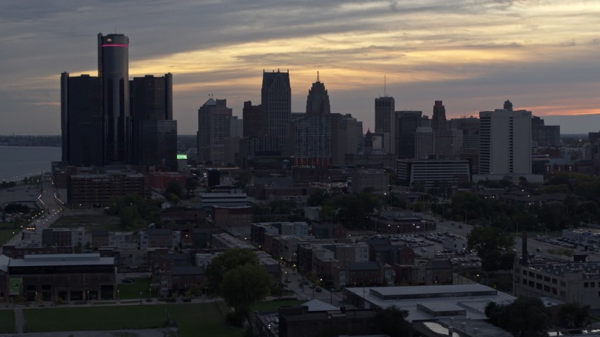 5.7K stock footage aerial video of descending past the city's tall skyscrapers at sunset, Downtown Detroit, Michigan Aerial Stock Footage | DX0002_197_047