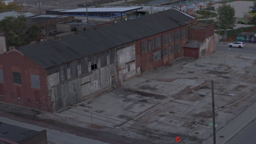 5.7K stock footage aerial video ascend away from an abandoned brick building at sunset, Detroit, Michigan Aerial Stock Footage | DX0002_197_051