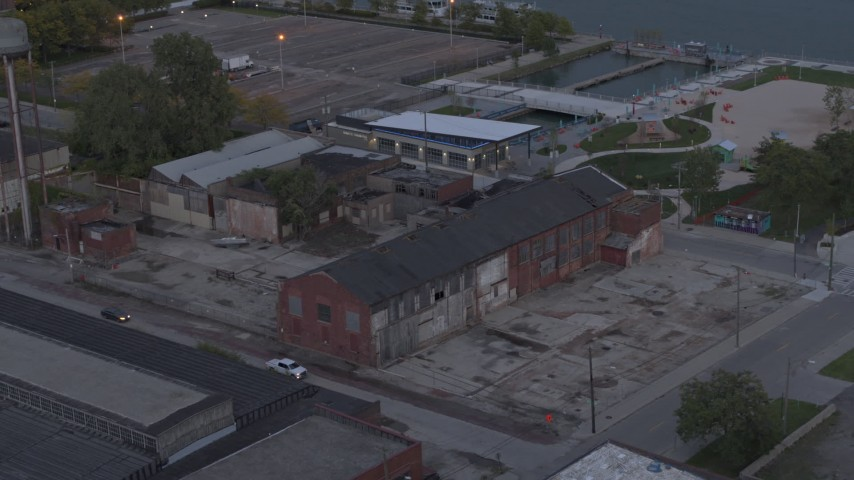 5.7K stock footage aerial video flying away from an abandoned brick building at sunset, Detroit, Michigan Aerial Stock Footage | DX0002_197_052