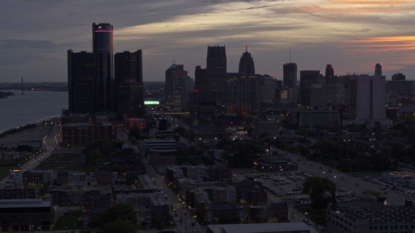 5.7K stock footage aerial video of flying away from and by the city's towering skyscrapers at sunset, Downtown Detroit, Michigan Aerial Stock Footage | DX0002_198_005