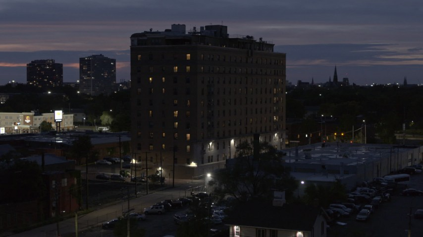 5.7K stock footage aerial video descend and circle an apartment building at twilight, Detroit, Michigan Aerial Stock Footage | DX0002_198_024