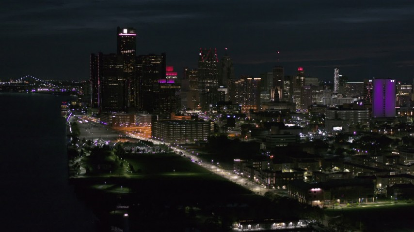 5.7K stock footage aerial video of the brightly lit skyscrapers in the city skyline at night, seen from the river, Downtown Detroit, Michigan Aerial Stock Footage | DX0002_198_038