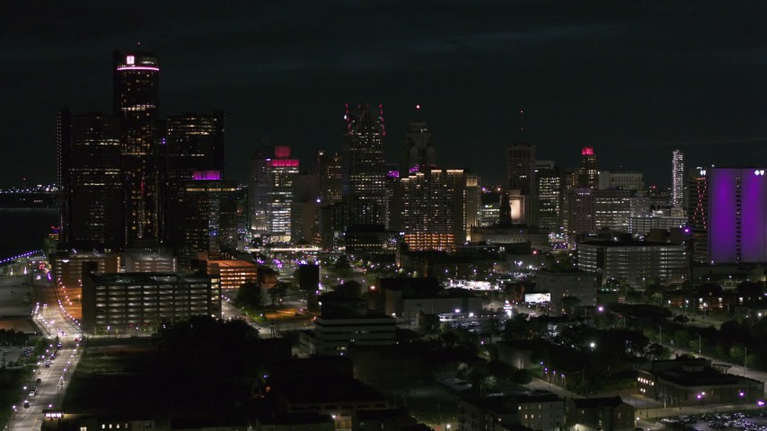 5.7K stock footage aerial video ascend and fly away from the skyline at night, Downtown Detroit, Michigan Aerial Stock Footage | DX0002_198_050