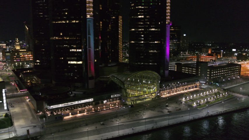 5.7K stock footage aerial video flyby parking lot to reveal entrance to GM Renaissance Center at night, Downtown Detroit, Michigan Aerial Stock Footage | DX0002_199_003