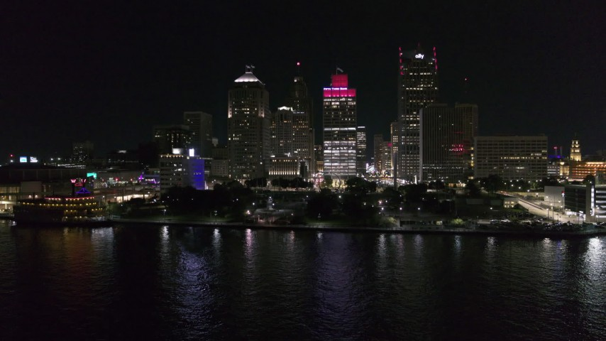5.7K stock footage aerial video focus on Hart Plaza and towering skyscrapers at night while descending by river, Downtown Detroit, Michigan Aerial Stock Footage | DX0002_199_013
