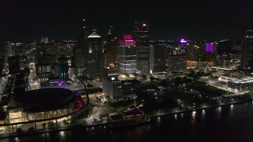 5.7K stock footage aerial video slowly orbit Hart Plaza and skyscrapers at night, seen from the river, Downtown Detroit, Michigan Aerial Stock Footage | DX0002_199_019