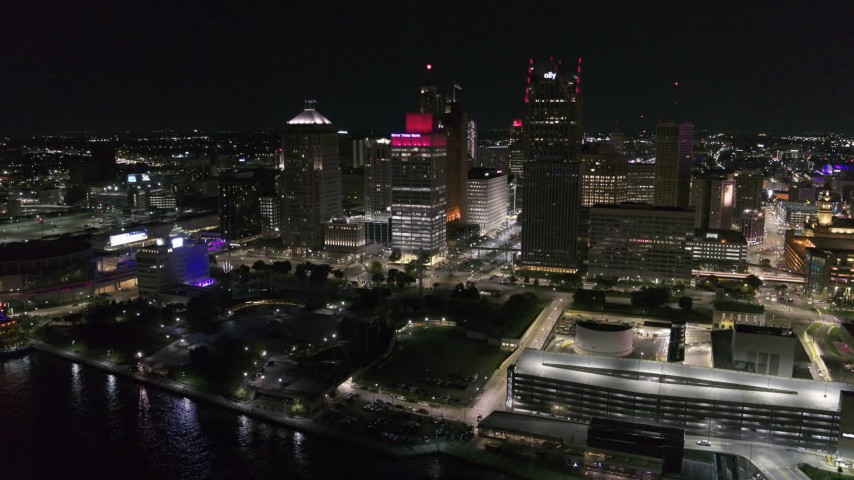 5.7K stock footage aerial video of orbiting Hart Plaza by tall skyscrapers at night, seen from the river, Downtown Detroit, Michigan Aerial Stock Footage | DX0002_199_021