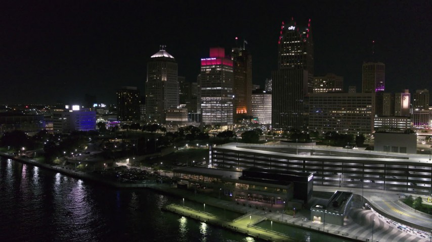 5.7K stock footage aerial video of Hart Plaza by tall skyscrapers at night, seen from the river, Downtown Detroit, Michigan Aerial Stock Footage | DX0002_199_022