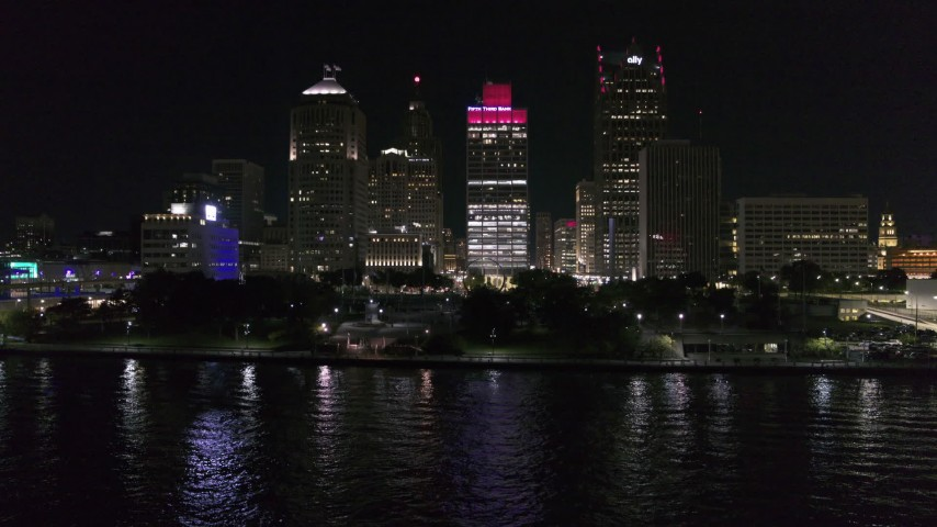 5.7K stock footage aerial video descend by riverfront Hart Plaza, focus on tall skyscrapers at night, Downtown Detroit, Michigan Aerial Stock Footage | DX0002_199_025