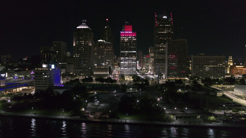 5.7K stock footage aerial video ascend by riverfront Hart Plaza, focus on tall skyscrapers at night, Downtown Detroit, Michigan Aerial Stock Footage | DX0002_199_026