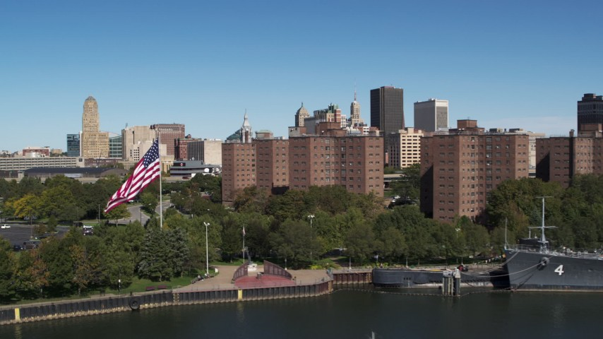 5.7K stock footage aerial video flying away from Downtown Buffalo and apartment complex, reveal warship, New York Aerial Stock Footage | DX0002_200_001