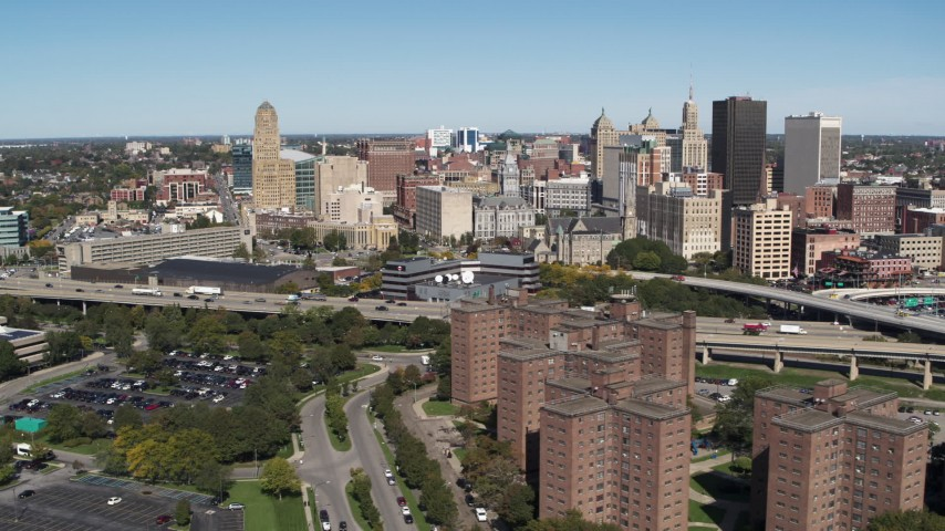 5.7K stock footage aerial video of the city's skyline seen while passing apartment buildings, Downtown Buffalo, New York Aerial Stock Footage | DX0002_200_010