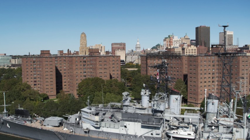 5.7K stock footage aerial video ascend past apartment buildings and warship to focus on skyline, Downtown Buffalo, New York Aerial Stock Footage | DX0002_200_015