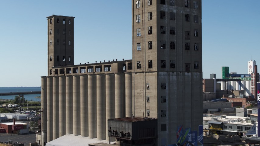 5.7K stock footage aerial video of descending beside a large grain elevator in Buffalo, New York Aerial Stock Footage | DX0002_201_026