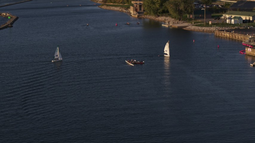 5.7K stock footage aerial video fly away from a rowboat and speedboat as sailboats arrive at sunset, Buffalo, New York Aerial Stock Footage | DX0002_203_036