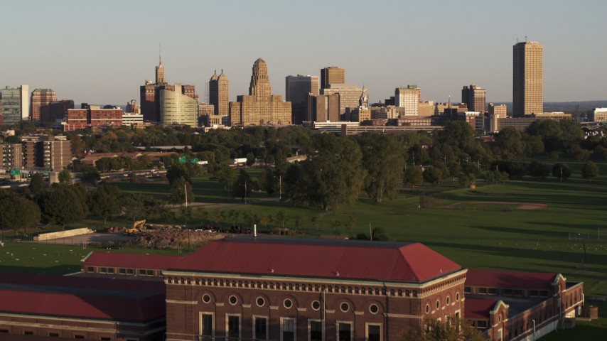 5.7K stock footage aerial video ascend over water filtration plant to approach city hall and skyline at sunset, Downtown Buffalo, New York Aerial Stock Footage | DX0002_203_037