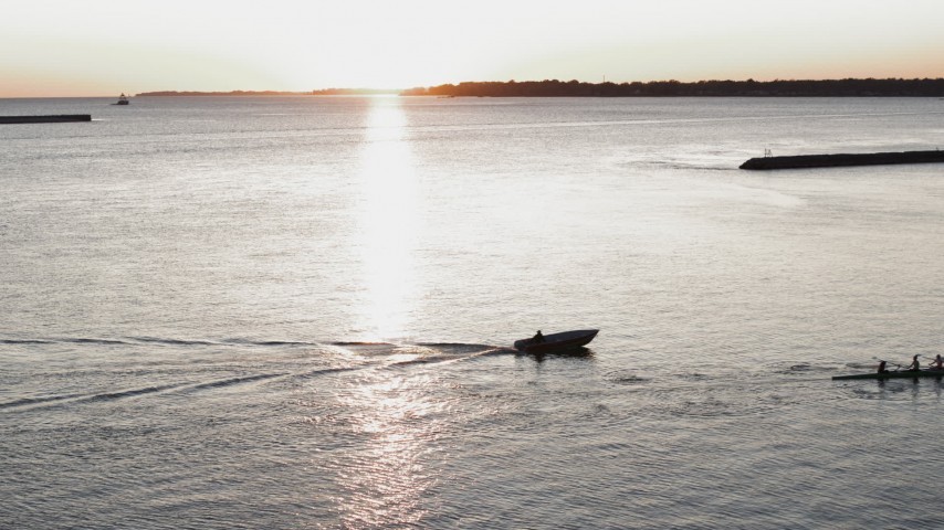 5.7K stock footage aerial video of a stationary view of Lake Erie as a rowboat and speedboat pass at sunset, Buffalo, New York Aerial Stock Footage | DX0002_204_013