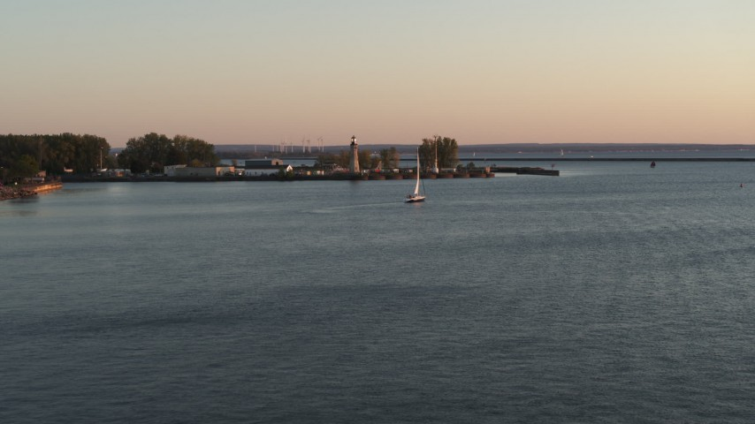 5.7K stock footage aerial video flying toward a sailboat on Lake Erie near lighthouse at sunset, Buffalo, New York Aerial Stock Footage | DX0002_204_015