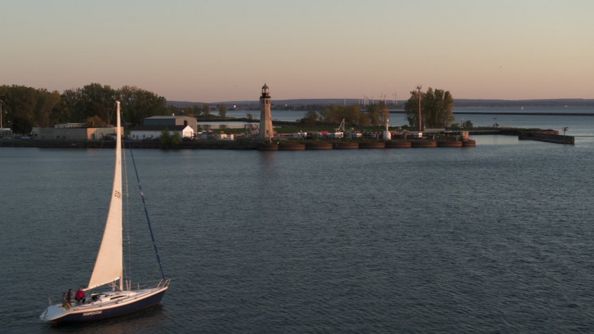 5.7K stock footage aerial video flying around a sailboat on Lake Erie toward lighthouse at sunset, Buffalo, New York Aerial Stock Footage | DX0002_204_016
