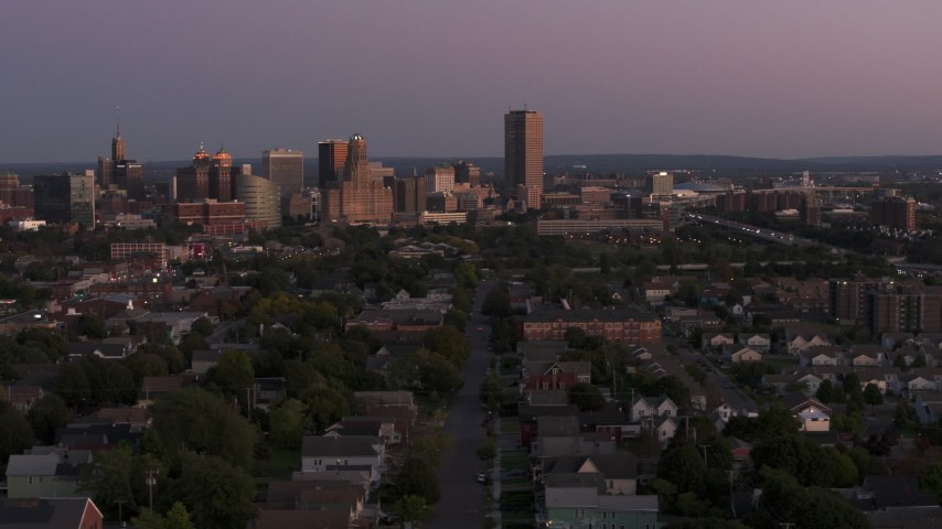 5.7K stock footage aerial video of Seneca One Tower and the city's skyline while passing homes at twilight, Downtown Buffalo, New York Aerial Stock Footage | DX0002_204_035