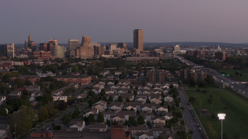5.7K stock footage aerial video of Seneca One Tower and skyline seen while passing homes at twilight, Downtown Buffalo, New York Aerial Stock Footage | DX0002_204_036