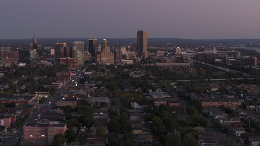 5.7K stock footage aerial video of Seneca One Tower and skyline seen while descending past homes at twilight, Downtown Buffalo, New York Aerial Stock Footage | DX0002_204_037