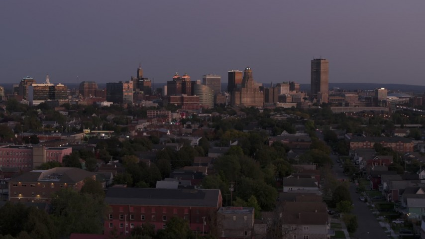 5.7K stock footage aerial video of the skyline seen while descending near apartments at twilight, Downtown Buffalo, New York Aerial Stock Footage | DX0002_204_039