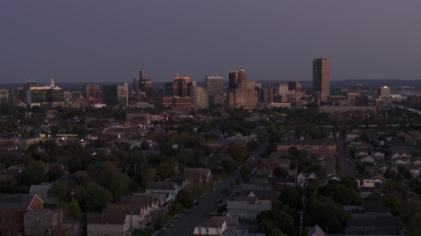 5.7K stock footage aerial video of the skyline seen while ascending past apartments and homes at twilight, Downtown Buffalo, New York Aerial Stock Footage | DX0002_204_040