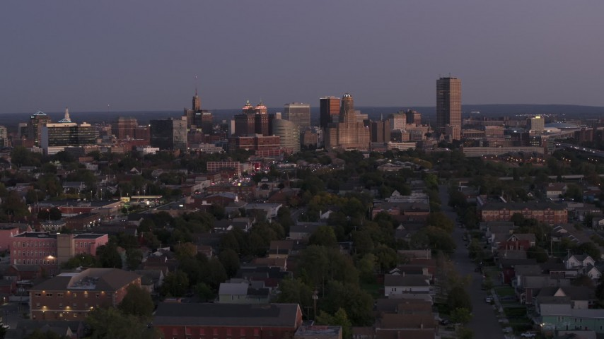 5.7K stock footage aerial video of descending past the skyline seen from apartments and homes at twilight, Downtown Buffalo, New York Aerial Stock Footage | DX0002_204_042