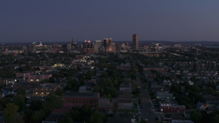 5.7K stock footage aerial video of the skyline while passing by apartments and homes at twilight, Downtown Buffalo, New York Aerial Stock Footage | DX0002_204_044