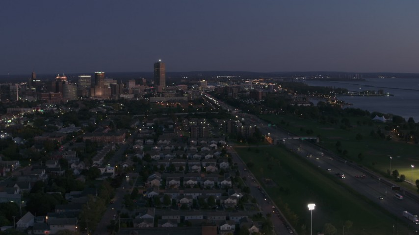 5.7K stock footage aerial video of skyscraper seen from I-190 and neighborhoods at twilight, Downtown Buffalo, New York Aerial Stock Footage | DX0002_204_046