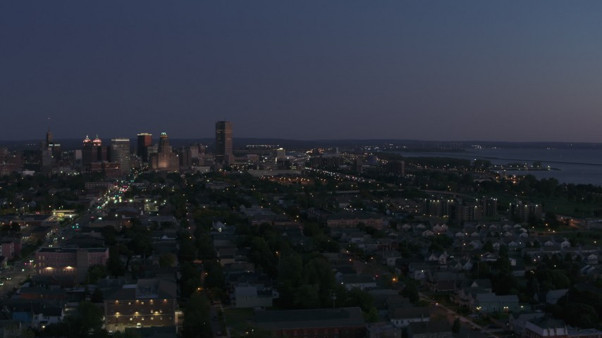 5.7K stock footage aerial video of skyscraper seen from I-190 and homes at twilight, Downtown Buffalo, New York Aerial Stock Footage | DX0002_204_047
