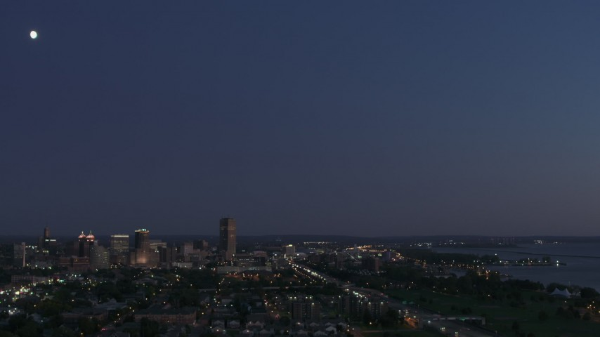 5.7K stock footage aerial video of the moon high above the city's skyline at twilight, Downtown Buffalo, New York Aerial Stock Footage | DX0002_204_048
