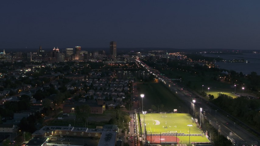 5.7K stock footage aerial video ascend near soccer field and I-190 for view of skyline at twilight, Downtown Buffalo, New York Aerial Stock Footage | DX0002_204_053