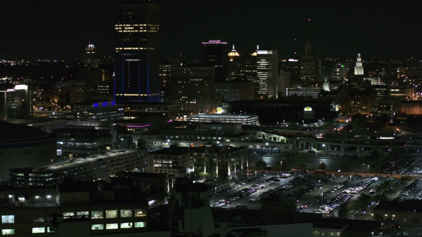 5.7K stock footage aerial video of the skyline seen while passing parking lots at night, Downtown Buffalo, New York Aerial Stock Footage | DX0002_205_033