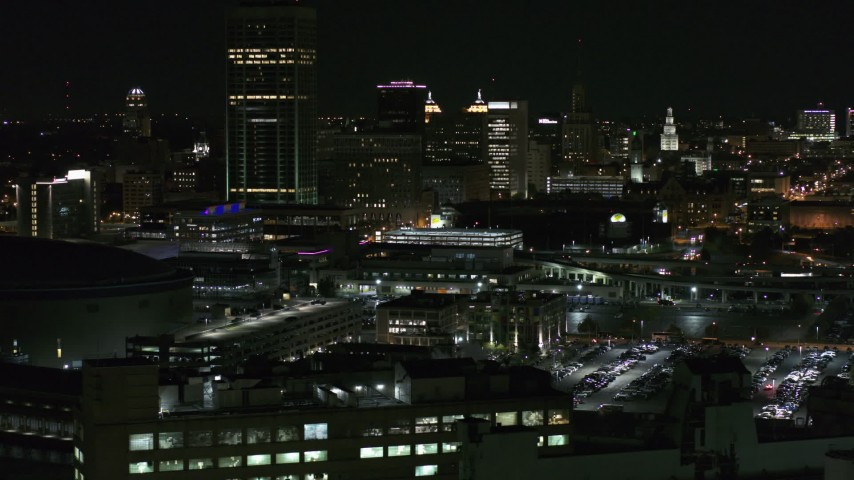 5.7K stock footage aerial video of flying by the skyline seen from parking lots at night, Downtown Buffalo, New York Aerial Stock Footage | DX0002_205_034