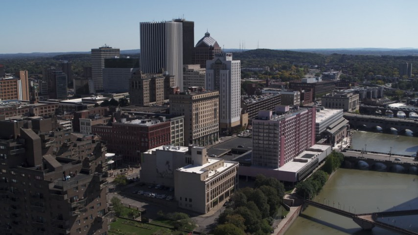 5.7K stock footage aerial video ascend away from riverfront hotels and the city's skyline, Downtown Rochester, New York Aerial Stock Footage | DX0002_206_002
