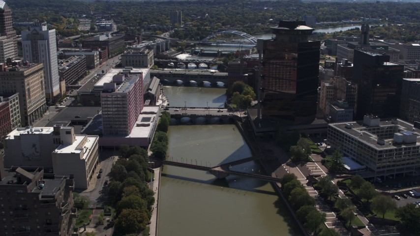 5.7K stock footage aerial video fly away from riverfront hotel across Genessee River from office building, Downtown Rochester, New York Aerial Stock Footage | DX0002_206_011