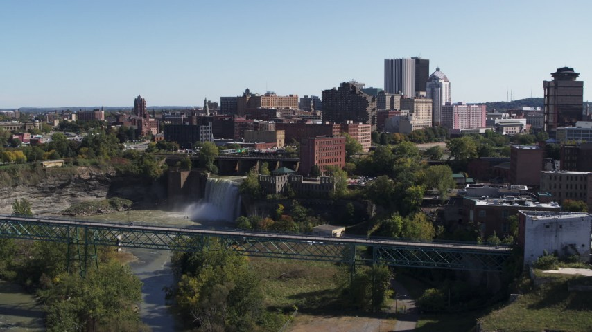 5.7K stock footage aerial video of the city's skyline behind waterfalls on the river, Downtown Rochester, New York Aerial Stock Footage | DX0002_206_027