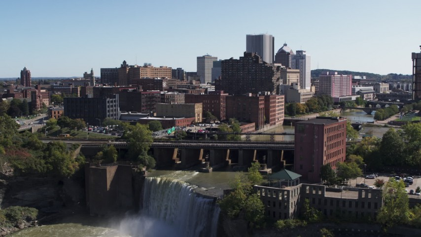 5.7K stock footage aerial video approach the city's skyline behind waterfalls on the river, Downtown Rochester, New York Aerial Stock Footage | DX0002_206_028