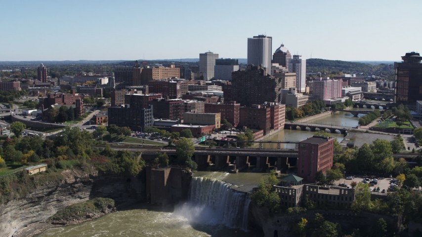 5.7K stock footage aerial video fly away from the city's skyline to reveal waterfalls on the river, Downtown Rochester, New York Aerial Stock Footage | DX0002_206_029