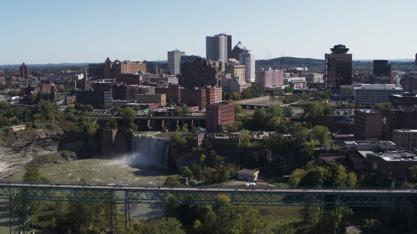 5.7K stock footage aerial video focus on the city's skyline behind waterfalls and river during descent, Downtown Rochester, New York Aerial Stock Footage | DX0002_206_030