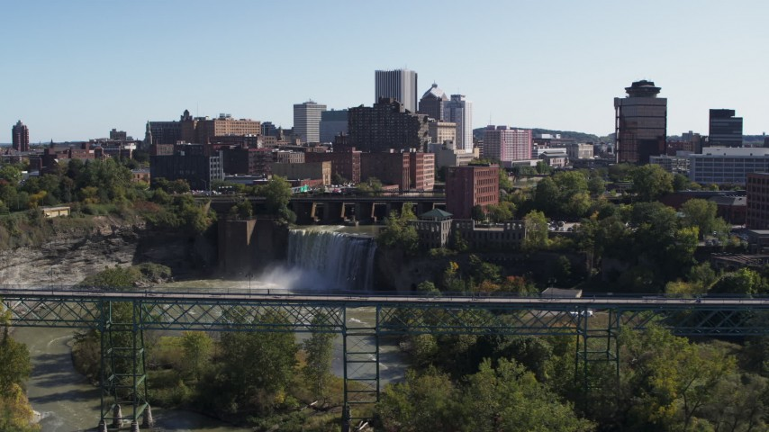 5.7K stock footage aerial video approach the city's skyline behind waterfalls and river from bridge, Downtown Rochester, New York Aerial Stock Footage | DX0002_206_031