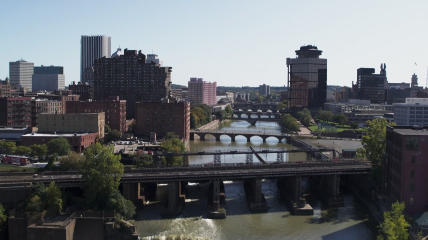 5.7K stock footage aerial video fly over falls and river bridges toward First Federal Plaza, Downtown Rochester, New York Aerial Stock Footage | DX0002_206_035