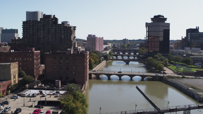 5.7K stock footage aerial video fly away from First Federal Plaza and bridges to reveal High Falls, Downtown Rochester, New York Aerial Stock Footage | DX0002_206_036