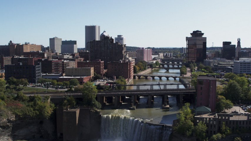 5.7K stock footage aerial video ascend over falls for view of river bridges and skyline Downtown Rochester, New York Aerial Stock Footage | DX0002_207_003