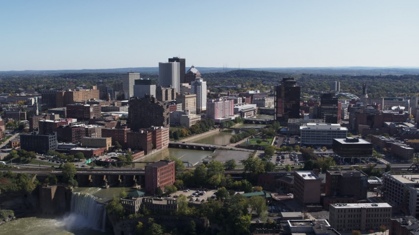 5.7K stock footage aerial video focus on skyline by river bridges while flying near waterfall, Downtown Rochester, New York Aerial Stock Footage | DX0002_207_007