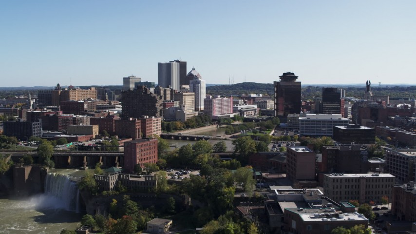 5.7K stock footage aerial video descend past skyline and river bridges to reveal High Falls, Downtown Rochester, New York Aerial Stock Footage | DX0002_207_008
